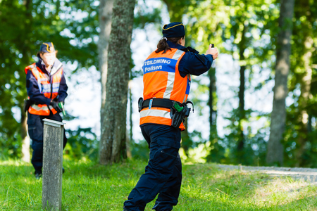 education in sweden: Vaxjo, Sweden - September 09, 2015: Police education. Outdoor weapons and apprehension training in public area. Female trainee with pepper spray in hand. Partner has gun out.