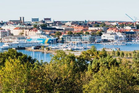 view on sea: Karlskrona, Sweden - September 07, 2015: View over Karlskrona as seen from Bryggarberget. The Coastguard 003 ship is moored close to marina. Church and other landmarks are seen in distance.