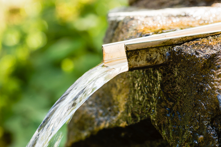 overflow: Fresh water flowing out from a overflow drainage in a stone setting. Shallow depth of field with blurred background. Weather is sunny and warm. Water is clean and fresh.