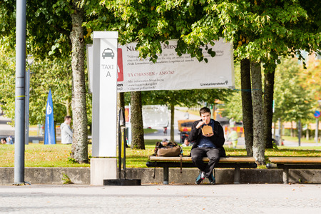 hectic: Vaxjo, Sweden - September 09, 2015: Unknown young adult man sit at a taxi and bus stop outside campus eating out of a box. He has bag beside him. Time efficiency is crucial for students.