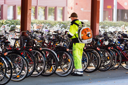 magnum: Vaxjo, Sweden - September 09, 2015: Unknown working man using a Stihl BR 600 Magnum blower to remove dry leaves from the bicycle parking place on university campus. Editorial