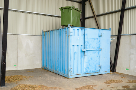 storage bin: Blue steel container with green trash bin on top. Container is outdoors but in an open storage space for protection.