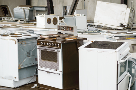 Old, used stoves and ovens are sorted separately at the waste station. Here are some that soon will be  transported away for dismantling and further recycling. Stock Photo