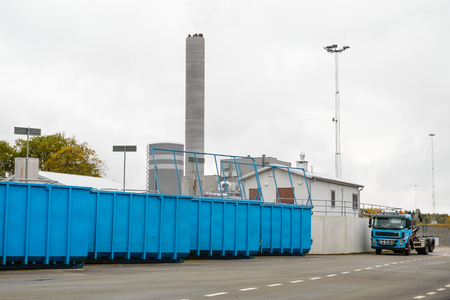 to fill up: Container truck is parked behind building waiting to shift waste containers as they fill up. Blue waste containers in foreground and combined heat and power plant in background. Stock Photo