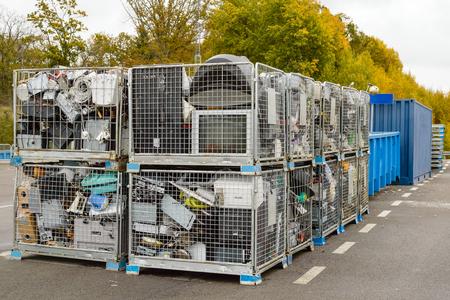Netted Körbe voll von Elektronikschrott entsorgt darauf warten, in den Papieranlage zur Weiterverarbeitung transportiert werden. Blaue Container im Hintergrund.