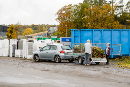 unsustainable: Bubbetorp, Sweden - October 21, 2015: Unknown senior couple unloads a trailer full of garden waste on the recycle dump. Sorted garden waste will often end up as compost after a year or two.