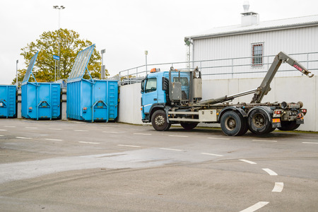 fill up: Bubbetorp, Sweden - October 21, 2015: Container truck parked at waste station ready to shift containers as they fill up. Waste is sorted in different containers for easy recycling.