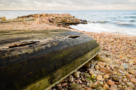 lies down: An upside down boat with a tarred, broken keel. Boat lies on pebble beach with the sea in the background. Damp weather and the sea is starting to break. Stock Photo