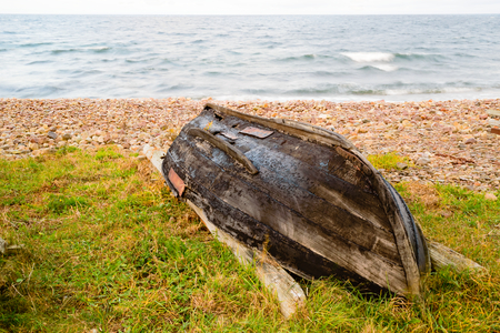 lies down: An upside down boat with a tarred, broken keel. Boat lies in the grass next to a pebble beach with the sea in the background. Damp weather and the sea is starting to break.
