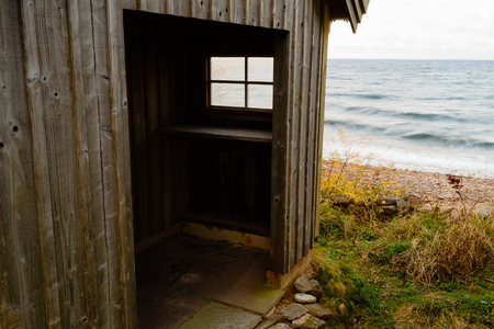 fishing cabin: An old fishing cabin with a small entrance under roof. Small window with view out to sea. Movement in the seawater in background. Stock Photo