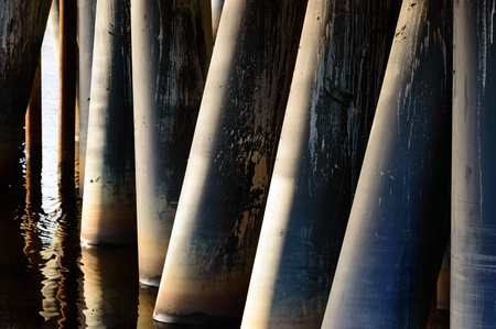 nonpolluting: Metal pillars or poles support a building standing in water. Fine reflections from the water surface. Stock Photo