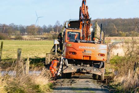 no pass: Kristianstad, Suecia - 12 de noviembre de 2015: la reparación del puente en un tramo estrecho de un senderismo trailin una reserva natural. A una persona está cavando a mano junto a una excavadora Doosan. Casi no hay espacio para pasar.