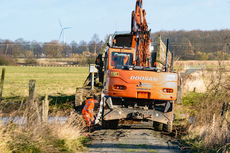 no pase: Kristianstad, Sweden - November 12, 2015: Bridge repair on a narrow stretch of a hiking trailin a nature reserve. One person is digging by hand beside a Doosan excavator. Almost no room to pass by.