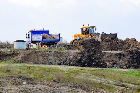 cargador frontal: Kristianstad, Suecia - 12 de noviembre de 2015: El antiguo vertedero está siendo lentamente transformó de un montón de basura a un área recreativa. Aquí un carro de depósitos poco de tierra cerca de una salida de gas hormigón.