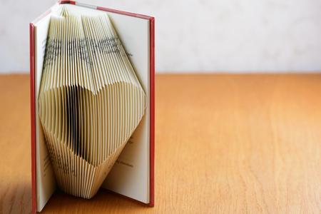 사랑스러운 마음을 형성하는 접힌 페이지와 서 책. 책 접기는 공예 공동체에서 매우 인기있는 예술 형식입니다. 공간을 오른쪽으로 복사하십시오.