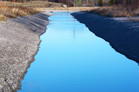 unsustainable: Gravel water purification trench or canal with calm and still urban runoff water. Sky is reflected in the water. Gravel is clean from vegetation.