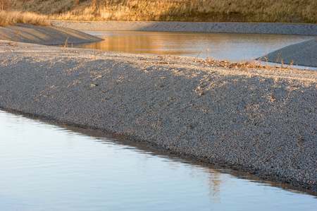 runoff: Gravel water purification trench or canal with calm and still urban runoff water. Sky is reflected in the water. Gravel is clean from vegetation.