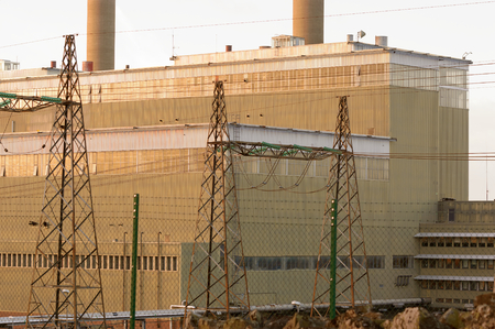 close up chimney: Close up of an oil fired thermal power station with electric cables in front of the main building, and tall flue gas stacks in the background. Stock Photo