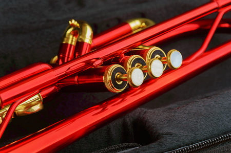 trumpet: A shining red trumpet with brass details. Trumpet is lying in black open case. Close up of instruments finger buttons, valve and slide.