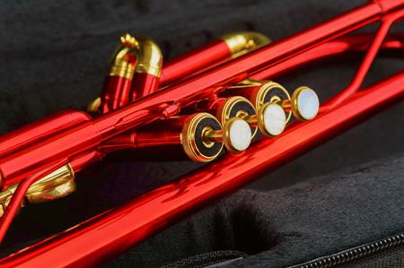 trompeta: Una trompeta de color rojo brillante con detalles de latón. Trompeta se ha quedado en la caja abierta negro. Cierre de botones dedo instrumentos, válvulas y diapositivas. Foto de archivo