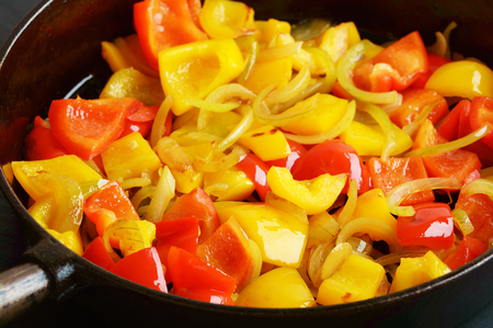 cast iron red: Red and yellow paprika with onions in a cast iron frying pan. Lovely fresh and tasteful combination for any dish. Reflections in the oily surface of the vegetables. Stock Photo