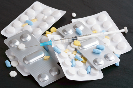 needle syringe infection: Syringe loaded with drug inside on a pile of other medication and blister packages. White and silver blister packages of medication with blue, yellow and white pills in a pile on dark background. Stock Photo