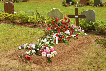 bury: A very fresh grave at a cemetery. A wooden cross with a white paper note for a name is a temporary headstone. Lovely flowers adorn the small pile of soil on top of the grave. Weather is damp. Stock Photo