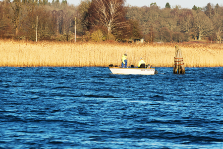 unusually: Ronneby, Sweden - December 30, 2015: Two unknown persons in a small open Crescent boat, ready to start fishing. It is an unusually warm winter this year with no ice or snow so far. Editorial