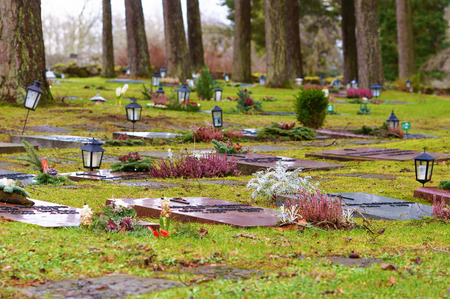 esthetics: Ronneby, Sweden - December 23, 2015: Lying red granite headstones at Bredakra cemetery. Lanterns are placed by some stones. Pine trees stand by the stones.  Nature is close at this graveyard. Editorial