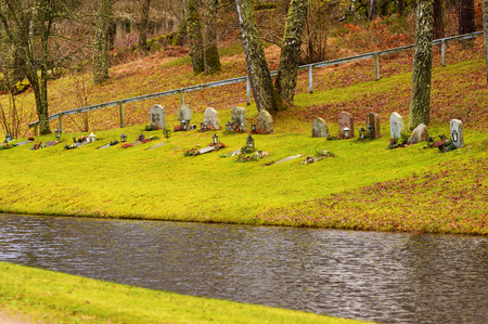 esthetics: Ronneby, Sweden - December 23, 2015: Gravestones close to a water pond at Bredakra cemetery. Trees surround the graves and nature plays a vital role in the esthetics of the place. Weather is damp. Editorial