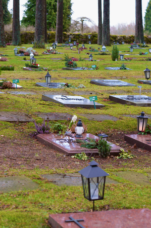headstones: Ronneby, Sweden - December 23, 2015: Lying red granite headstones at Bredakra cemetery. Lanterns are placed by some stones. Pine trees stand by the stones.  Nature is close at this graveyard. Editorial