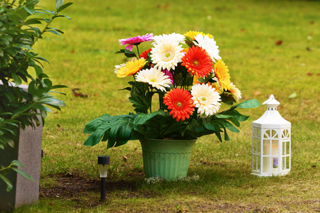 pot light: Colorful plastic flower in a pot beside an unknown headstone. A small white lantern with candle inside stand beside pot. Smaller black solar powered lamp stuck in the ground as well.