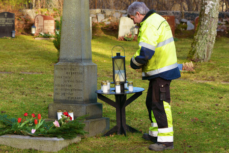 stone tombstone: Ronneby, Sweden - December 29, 2015: Unknown male graveyard worker standing beside the memorial tombstone of unnamed persons. Small table with lanterns in front of man.