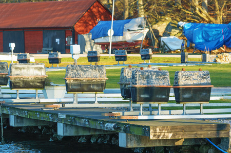 floaters: Upside down mooring rigs with floaters resting on land so they do not break during icy winter conditions. Storage building and covered boats in background. Stock Photo