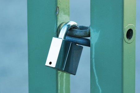 hardened: A solid padlock hold a green metal gate closed. Padlock is shiny and reflects the sky. Stock Photo