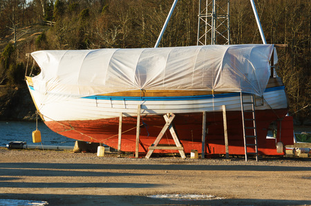 sheeting: Boats in winter storage covered with tarps and supported by scaffoldings. Winter storage on land protects the boats from the sea ice that could otherwise cause damage to the keels. Stock Photo