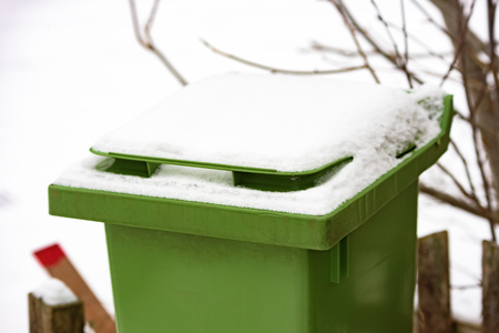 Snow covered green trash bin lid in winter.