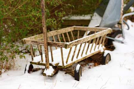 coldness: A small and weathered wooden wagon or trolley with light snow cover beside some shrubbery. Trolley is unpainted. Stock Photo