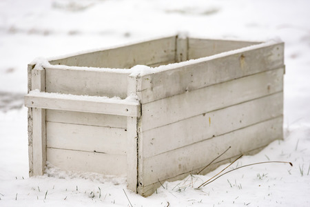 coldness: A white open wooden box standing in the snow. Shallow focus on front corner.