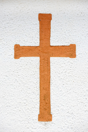 sanctified: An orange Christian cross on a white stone wall. Stock Photo