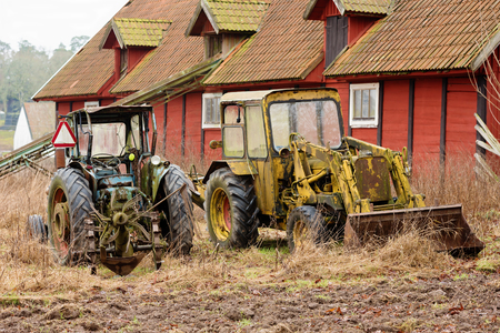 old barn in winter: Old vintage tractors stand outside a farm building or barn. They are parked in high grass and rich soil. Weather is damp, season is fall or winter. Different farming tools are attached to the vehicles.
