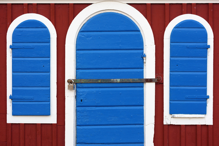 red shutters: Blue door and shutters on a red shack. Door and shutters are framed in white. Iron bar in front of door is locked by padlock. Stock Photo