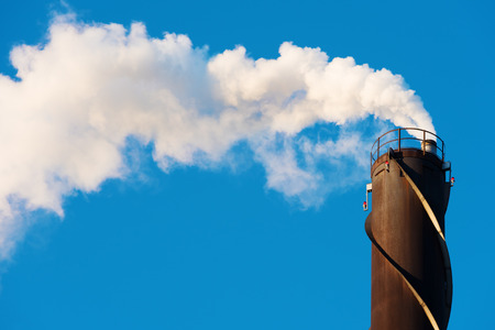tall chimney: White, water rich smoke comes out of a tall chimney against a clear blue sky. Chimney has red position lights and spiraling vortex dampeners. Copy space in sky. Stock Photo