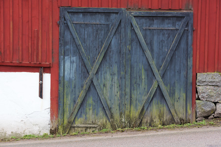 barn doors: Two closed barn doors. The road in front is slightly tilted. Barn is red with black doors, Doors are dirty close to ground. Stock Photo