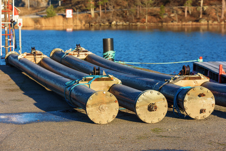 dockside: Sea cable housing tubes on the dockside in a coastal bay waiting to be deployed at sea. Sea in background. Stock Photo
