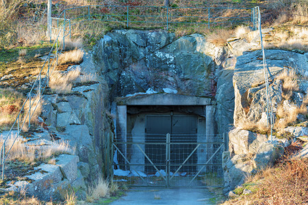 secretive: A rock shelter in the mountainside. A closed steel door and anonymous barbed wire fencing suggest military or other secretive organizations installation.