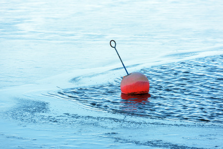 A red mooring buoy floats in some open water with ice closing in or melting.