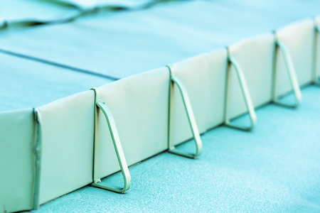 hindrance: Close up of metal snow guard on roof. Shallow focus on front part of railing. Stock Photo