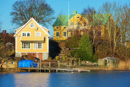 sea of houses: Karlskrona, Sweden - January 13, 2016: Many homes lie close to water and nature in the coastal travel location of Karlskrona. Two yellow houses and a greenhouse near the sea. Editorial
