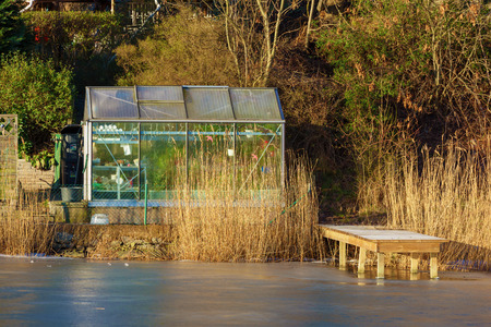 Karlskrona, Sweden - January 13, 2016: Karlskrona is a lovely travel location even in winter. Here a glass greenhouse close to the ice covered sea. A small wooden jetty stretch into the ice. Editorial